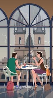 Um jovem casal com café se senta a uma mesa em frente à igreja em praga, na praça velha.