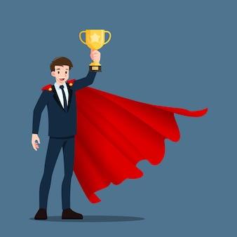Um jovem empresário de sucesso usa uma capa vermelha e levanta uma taça de troféu de ouro.