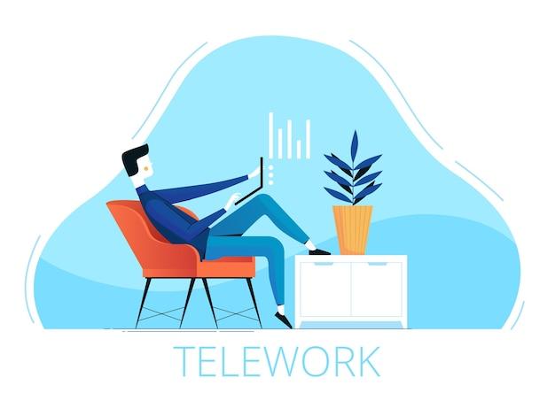 Um jovem freelancer do sexo masculino se senta em uma cadeira e trabalha remotamente de casa.