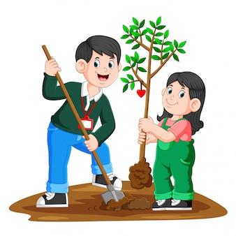 Um jovem pai e sua filha, plantando uma árvore