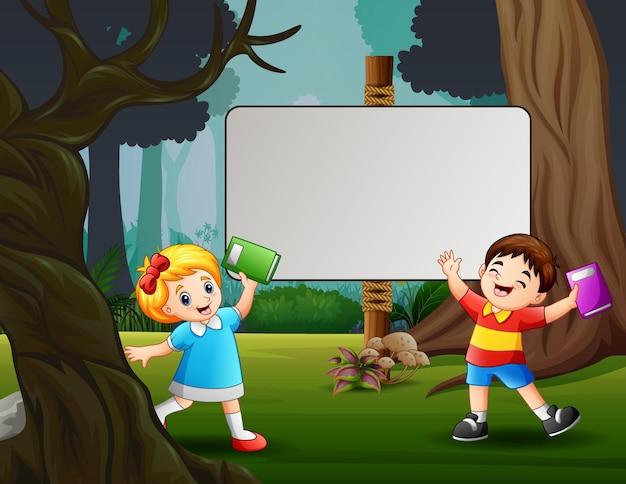 Um lindo menino e uma menina em pé perto da placa em branco