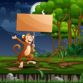 Um macaco segurando placa de madeira na floresta