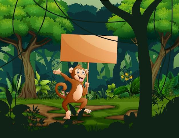 Um macaco segurando uma placa de sinal de madeira vazia na floresta