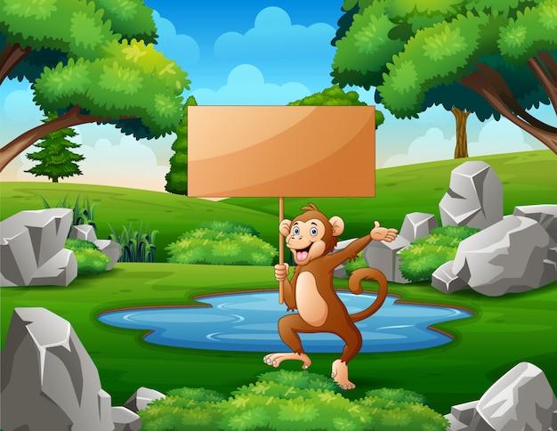 Um macaco segurando uma placa de sinal de madeira vazia no parque