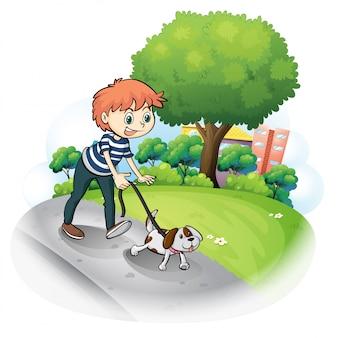 Um menino andando com seu cachorro ao longo da rua