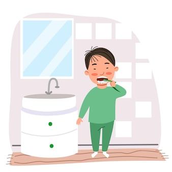 Um menino asiático de pijama verde escova os dentes no banheiro.
