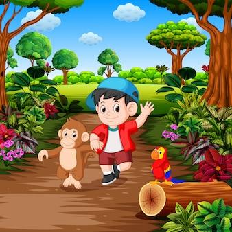 Um menino com macaco na floresta tropical