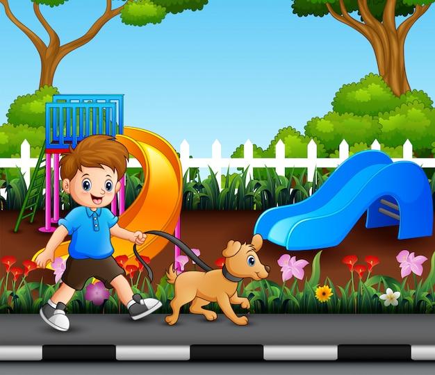 Um menino com seu animal de estimação andando no parque da cidade