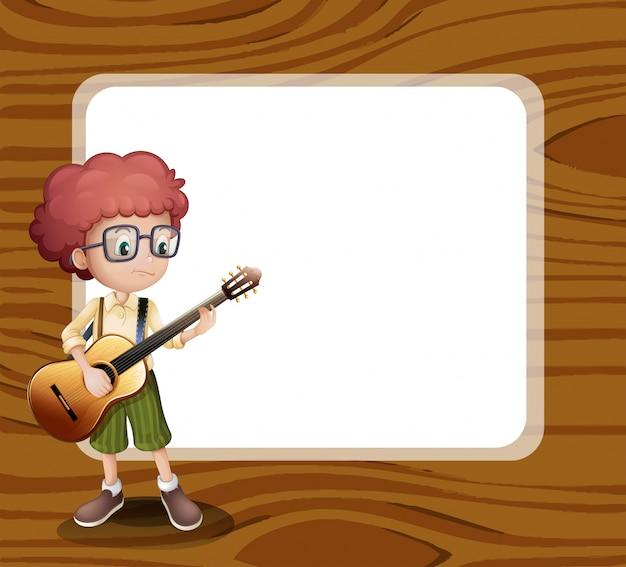 Um menino com um violão de pé na frente do modelo vazio