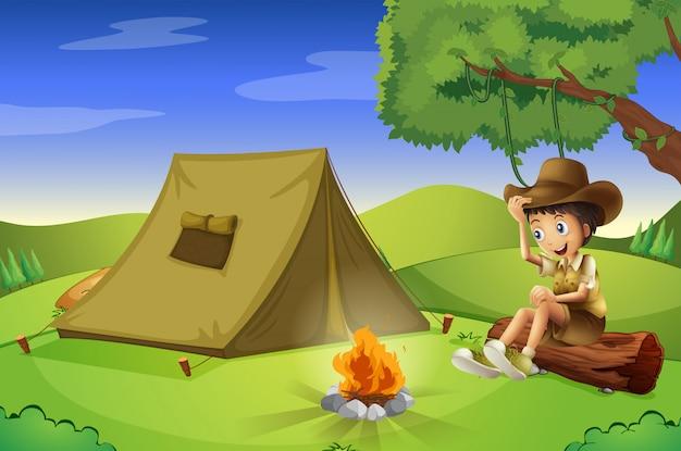 Um menino com uma tenda e uma fogueira
