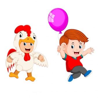 Um menino correndo segurando balão com crianças vestindo traje de galo