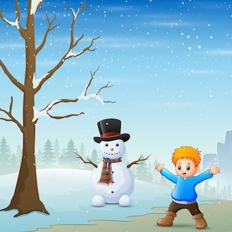 Um menino de pé perto do boneco de neve na paisagem de inverno