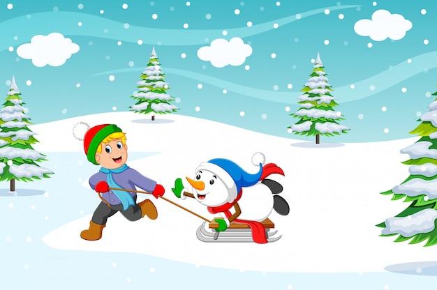 Um menino e casaco quente jogando um passeio de trenó com uma neve