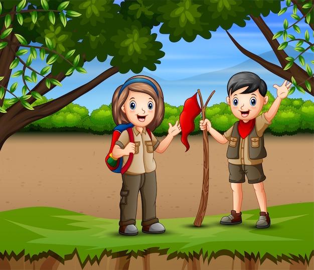 Um menino e uma escoteira caminhadas na floresta