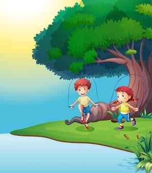 Um menino e uma menina brincando perto da árvore gigante