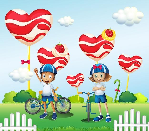 Um menino e uma menina de bicicleta perto dos pirulitos gigantes