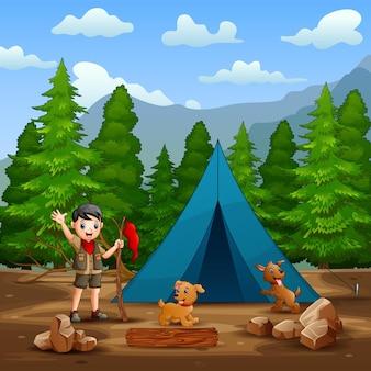 Um menino escoteiro e cachorros na frente da barraca