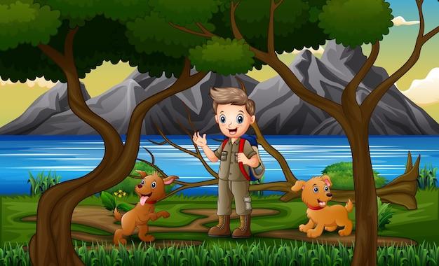 Um menino escoteiro e cachorros na paisagem da floresta