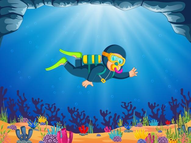 Um menino está mergulhando sob o lindo mar com o pano azul mergulhando