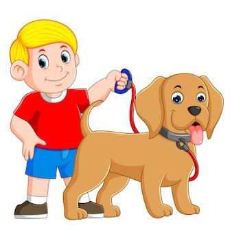 Um menino está segurando a corda vermelha e em pé ao lado do cão