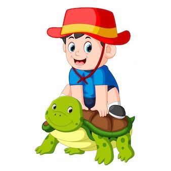 Um menino está sentado em uma grande tartaruga