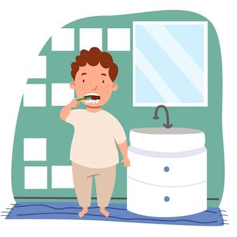 Um menino europeu de cabelos cacheados e sardas de pijama está escovando os dentes no banheiro.
