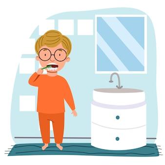 Um menino europeu de óculos e pijama está escovando os dentes no banheiro.