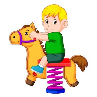 Um menino feliz brincar com cavalo marrom brinquedo
