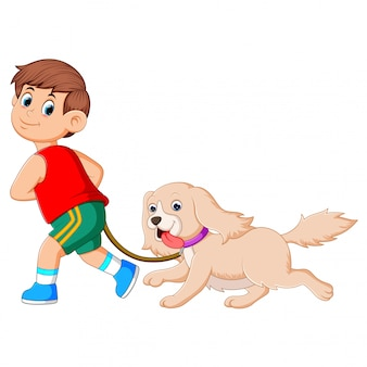 Um menino feliz está correndo e puxando seu lindo cachorro marrom