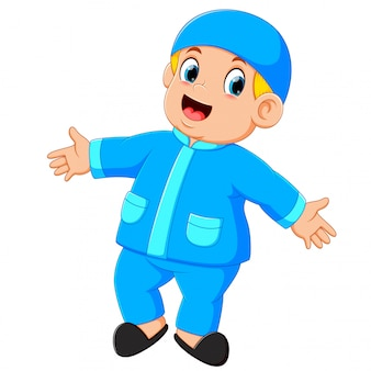 Um menino feliz está de pé e dançando com suas novas roupas azuis