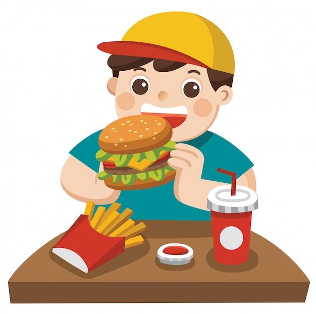 Um menino fofo come hambúrguer com batatas fritas e refrigerante