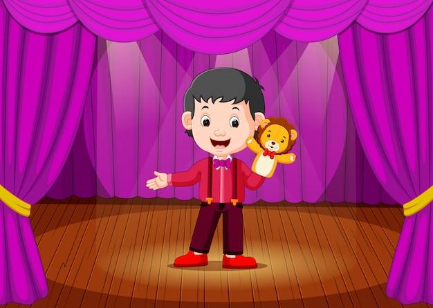 Um menino jogando fantoche no palco