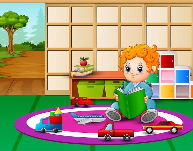 Um menino lendo livro na sala de aula