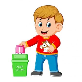 Um menino manter ambiente limpo por sapinho em caixote do lixo