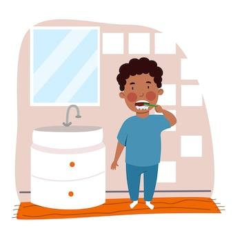 Um menino negro de pijama está escovando os dentes no banheiro crianças são higiene