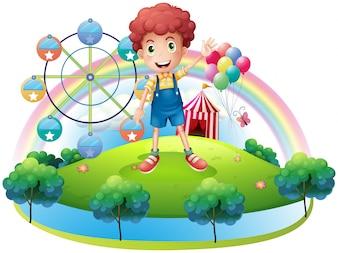 Um menino perto de um parque de diversões