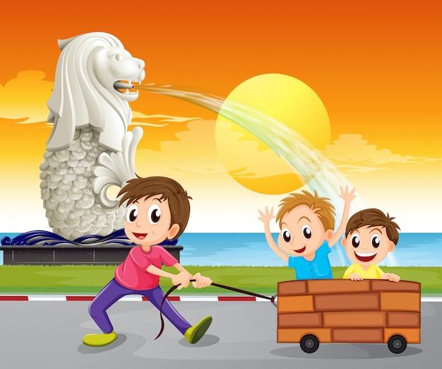 Um menino puxando um carrinho improvisado perto da estátua do merlion