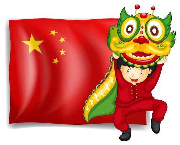 Um menino que faz a dança do dragão na frente da bandeira da china