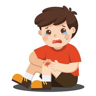 Um menino segurando uma ferida dolorosa na perna ferida no joelho