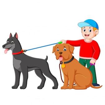 Um menino usando a camisola vermelha está de pé na parte de trás de dois cachorro grande