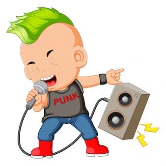 Um menino vestido como um rockstar cantando na frente de um alto-falante