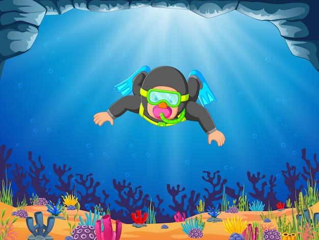 Um mergulhador profissional homem está mergulhando com as nadadeiras azuis