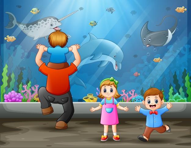 Um pai com filhos olhando peixes nadando
