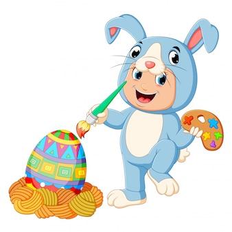 Um rapaz vestindo trajes de coelho e pintar um ovo