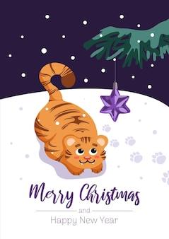 Um tigre fofo brinca com uma árvore de natal, uma estrela de brinquedo. símbolo do feliz natal do ano novo chinês de 2022