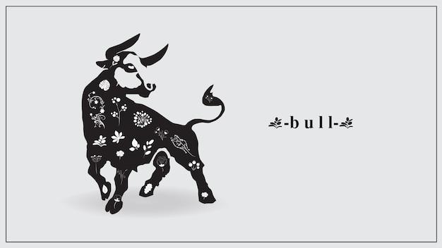 Um touro preto com flores e plantas brancas.