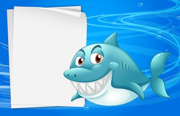 Um tubarão com um papel bond vazio sob o mar