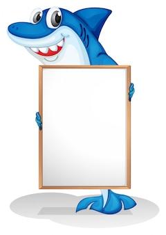 Um tubarão sorridente segurando um quadro branco vazio