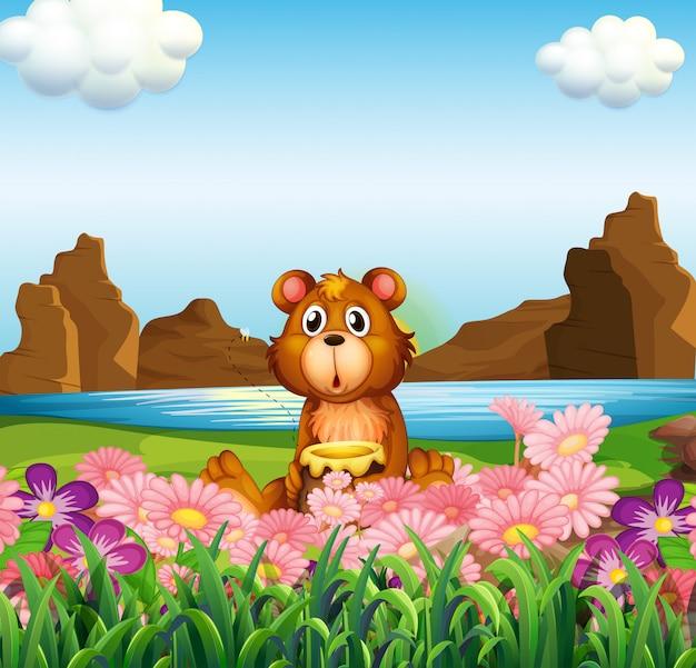 Um urso bonito perto das flores na margem do rio