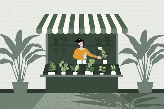 Um vendedor está sentado na loja vendendo diferentes variedades de árvores.